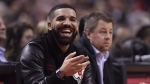 Drake smiles as he watches the Toronto Raptors play the Golden State Warriors during first half NBA basketball action in Toronto on Thursday Nov. 29, 2018. THE CANADIAN PRESS/Nathan Denette