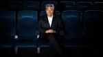 In this Feb. 6, 2013, file photo, Kevin Tsujihara, poses for photos in a screening room at the Warner Bros. Studios in Burbank, Calif. (AP Photo/Jae C. Hong)