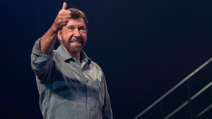 U.S. actor and martial artist Chuck Norris signals to the audience onstage during the opening gala of the 15th Shoe Box fundraising event in Papp Laszlo Sports Arena in Budapest, Hungary, Saturday, Nov. 24, 2018. (Marton Monus/MTI via AP)