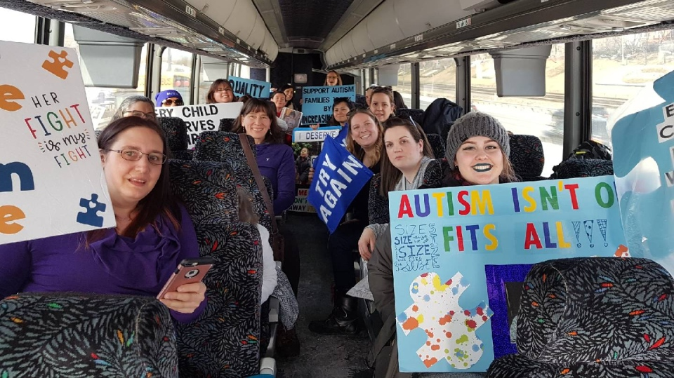 A busload of people heading to Queen's Park to protest changes to the province's autism program.