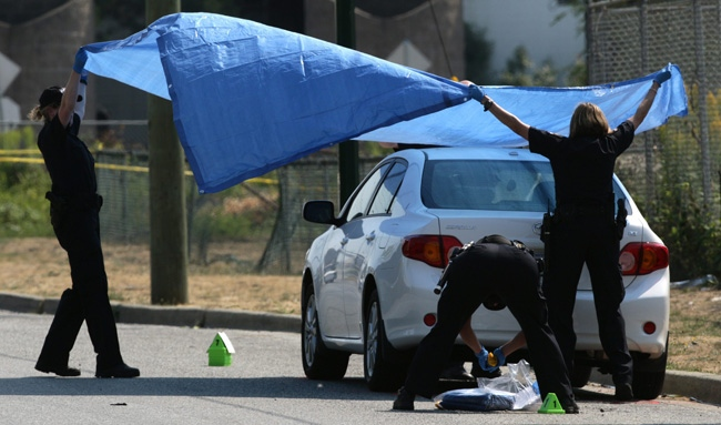 A police officer investigates after a body was found in the trunk of the car in Vancouver, B.C., on Wednesday July 29, 2009. (CP/Darryl Dyck)