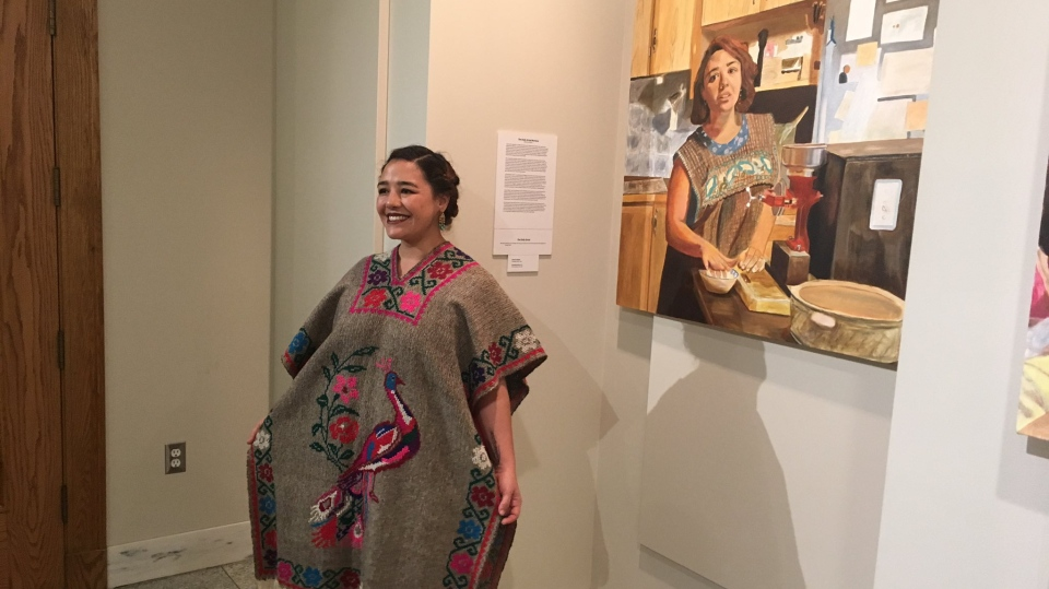 Mariana Brito, a subject of the exhibit by artist Madhu Kumar, stands beside Kumar's depiction of her at the exhibition's opening on Friday. (Cole Davenport/CTV Regina)