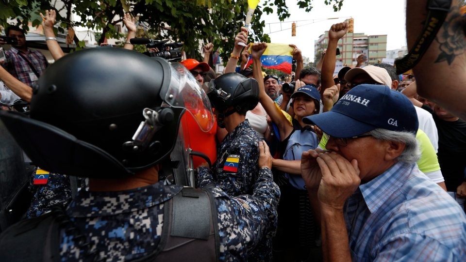Venezuelan opposition protesters confront police blocking their path, in Caracas, Venezuela, Saturday, March 9, 2019. Protesters vented their anger at security forces over a nationwide blackout, shortages of basic necessities and the government of President Nicolas Maduro. (AP Photo/Eduardo Verdugo)