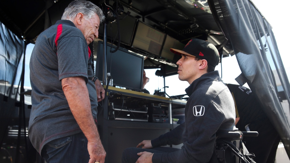 Auto racing legend Mario Andretti, left, talks with Robert Wickens at the IndyCar Grand Prix of St. Petersburg auto race in St. Petersburg, Fla., Friday, March 8, 2019. (Dirk Shadd/Tampa Bay Times via AP)