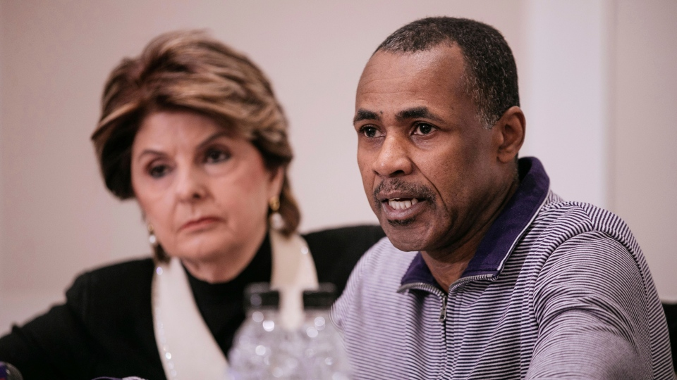 Gary Dennis, seated with Lawyer Gloria Allred, speaks during a press conference announcing a video tape said to present further evidence of wrongdoing by recording artist R. Kelly Saturday, March 10, 2019, in New York. (AP Photo/Kevin Hagen)