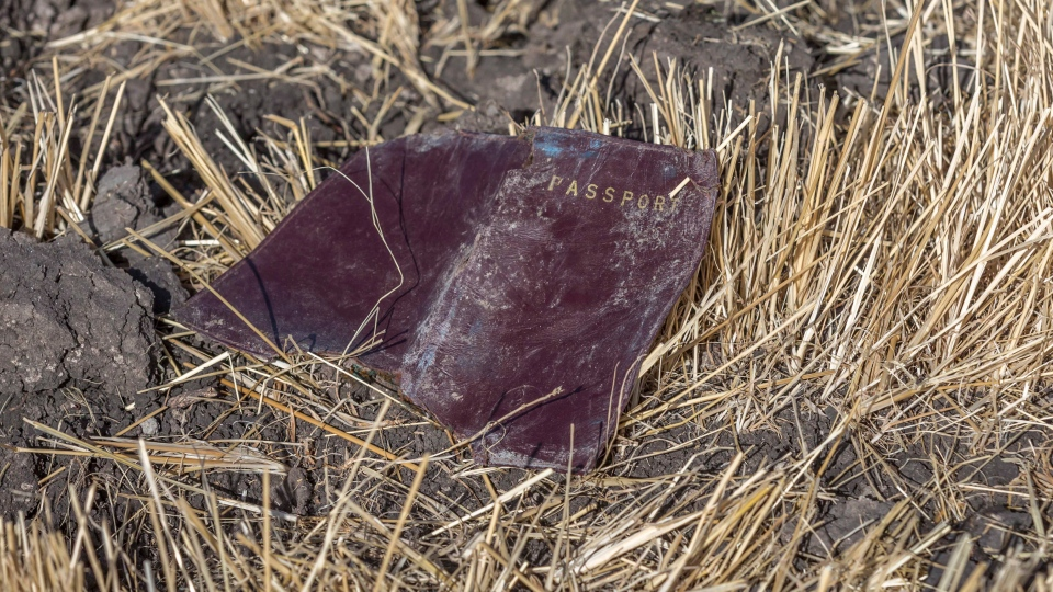 A passenger passport lies on the ground at the scene of an Ethiopian Airlines flight crash near Bishoftu, or Debre Zeit, south of Addis Ababa, Ethiopia, Monday, March 11, 2019. (AP Photo/Mulugeta Ayene)