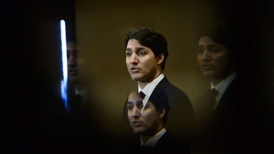 Prime Minister Justin Trudeau is pictured through a bevelled pane of glass in a door as he takes part in a press conference in Iqaluit, Nunavut on Friday, March 8, 2019. THE CANADIAN PRESS/Sean Kilpatrick