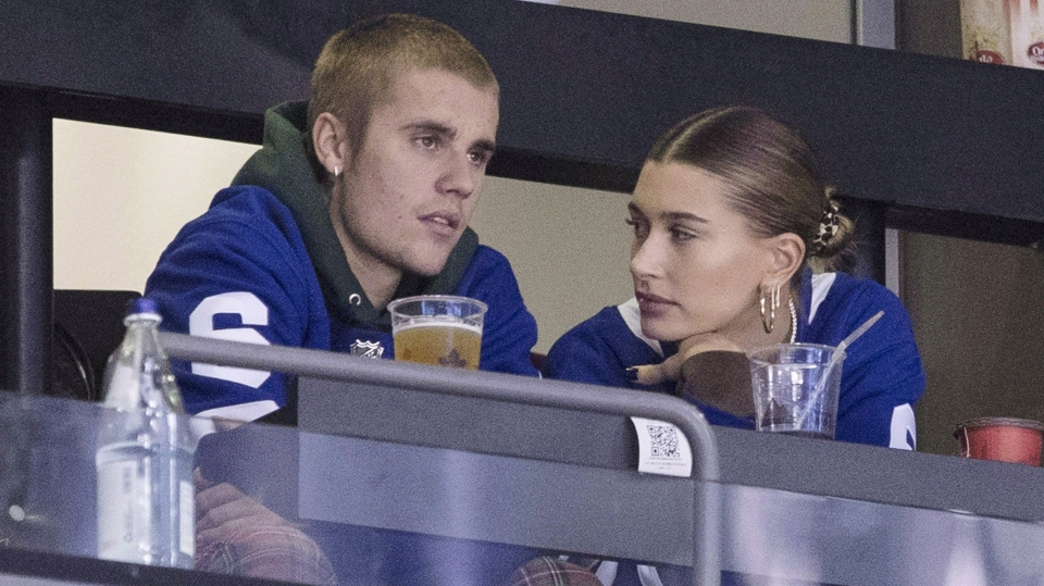 Justin Bieber watches alongside his wife Hailey Baldwin, right, during NHL hockey action between the Philadelphia Flyers and the Toronto Maple Leafs, in Toronto on Saturday, Nov. 24, 2018. Justin Bieber is asking his fans for emotional support as he works to face his personal struggles