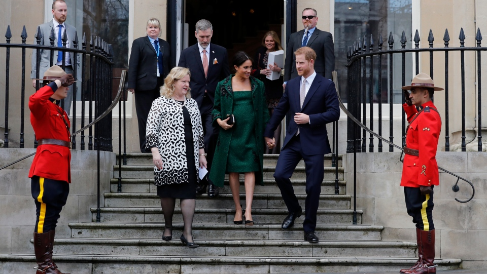 Prince Harry and Meghan, Duchess of Sussex are saluted by members of the Canadian Royal Mounted Police as they leave Canada House in London, Monday, March 11, 2019. (AP Photo/Alastair Grant)