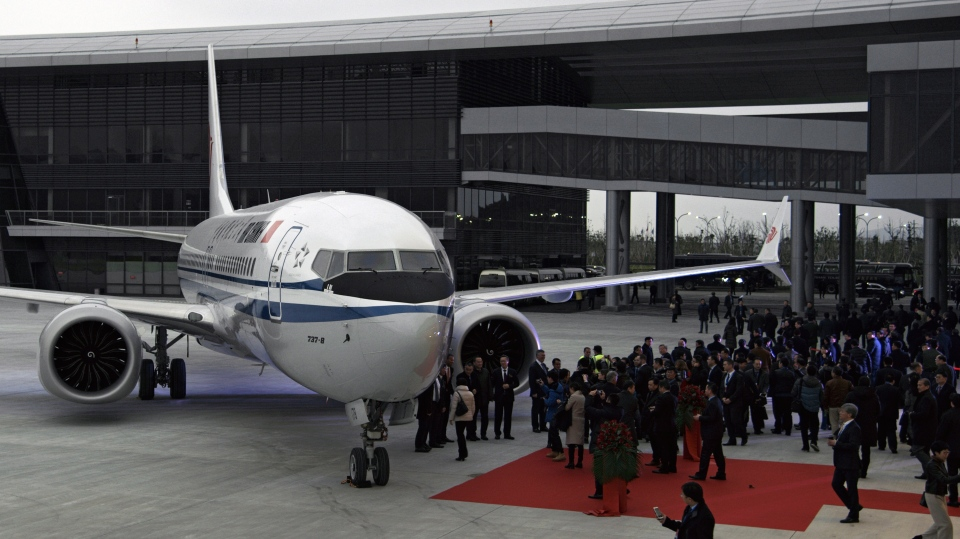 In this Dec. 15, 2018, photo, invited guests look at the Boeing 737 Max 8 airplane parked on tarmac after being delivered to Air China at Boeing Zhoushan 737 Completion and Delivery Center in Zhoushan, east China's Zhejiang Province. China's civilian aviation authority has ordered all Chinese airlines to ground their Boeing 737 Max 8 planes on Monday, March 11, 2019 after one of the aircraft crashed in Ethiopia. The authority said the one-day action was made out of safety concerns because the crash was similar to one in Indonesia last year. (Chinatopix via AP)