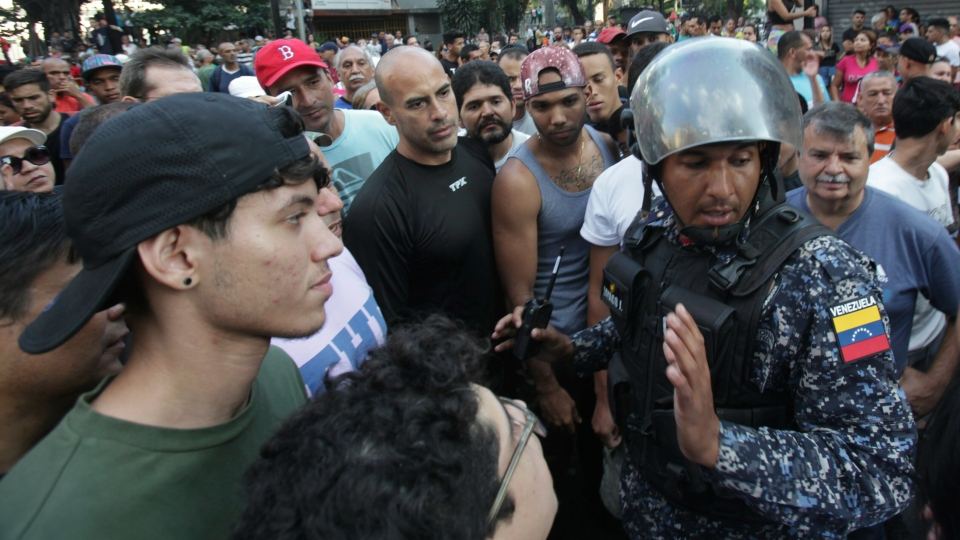 People surround a Venezuelan Bolivarian National Police officer during a protest against Venezuela's President Nicolas Maduro in Caracas, Venezuela, Saturday, March 9, 2019. (AP Photo/Boris Vergara)