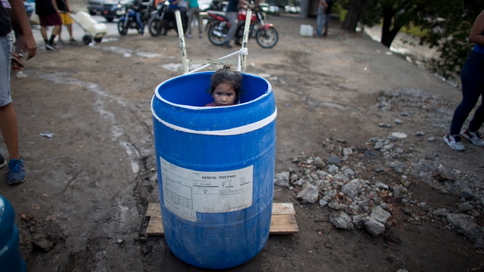 A little girl stands inside a plastic barrel while her family waits to collect water from an open pipe above the Guaire River, during rolling blackouts which affect the water pumps in people's homes, offices and stores, in Caracas, Venezuela, Monday, March 11, 2019. (AP Photo/Ariana Cubillos)