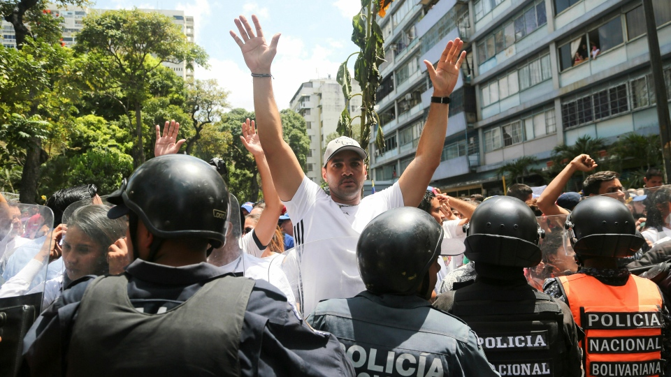Demonstrators confront a cordon of Venezuelan National Police officer who temporarily block members of the opposition from reaching a rally against the government of President Nicolas Maduro in Caracas, Venezuela, Saturday, March 9, 2019. (AP Photo/Fernando Llano)