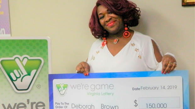 This Feb. 14, 2019 photo provided by Virginia Lottery shows Debrorah Brown holding up a check after winning the Pick 4 in Richmond, Va. (Virginia Lottery via AP)