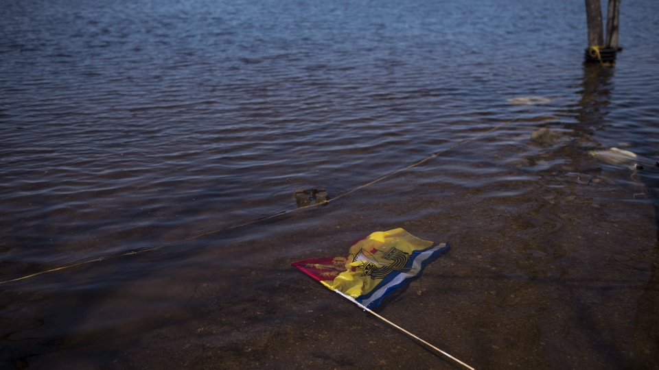 A year after record spring flooding in New Brunswick, officials say only Mother Nature knows if there will be a repeat this year. A New Brunswick flag floats in floodwater from the Saint John River in Waterborough, N.B., on Sunday, May 13, 2018. (THE CANADIAN PRESS/Darren Calabrese)