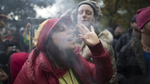 A woman smokes a marijuana cigarette during a legalization party at Trinity Bellwoods Park in Toronto, Ontario. (Geoff Robins / AFP)