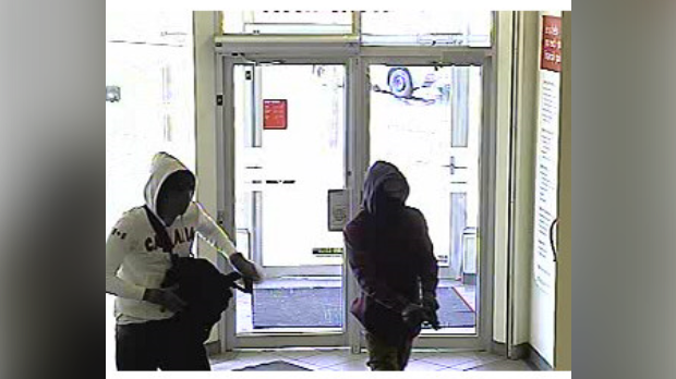 Police are seeking two suspects after a Cambridge bank was robbed at gunpoint. (Source: WRPS)