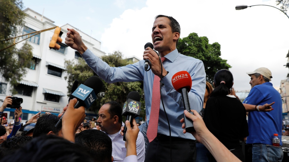 National Assembly President Juan Guaido, who declared himself interim president of Venezuela, speaks to supporters as he visits different points of anti-government protest in Caracas, Venezuela, Tuesday, March 12, 2019. (AP Photo/Ariana Cubillos)