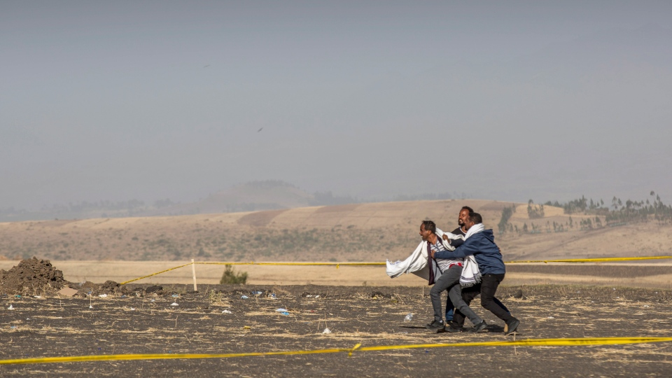 A grieving relative is held back by others at the scene where the Ethiopian Airlines Boeing 737 Max 8 crashed shortly after takeoff on Sunday killing all 157 on board, near Bishoftu, or Debre Zeit, south of Addis Ababa, in Ethiopia Wednesday, March 13, 2019. (AP Photo/Mulugeta Ayene)