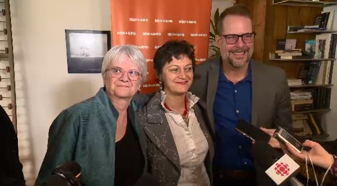 NDP candidate Nima Machouf, centre, is flanked by NDP MPs Helene Laverdiere and Alexandre Boulerice.