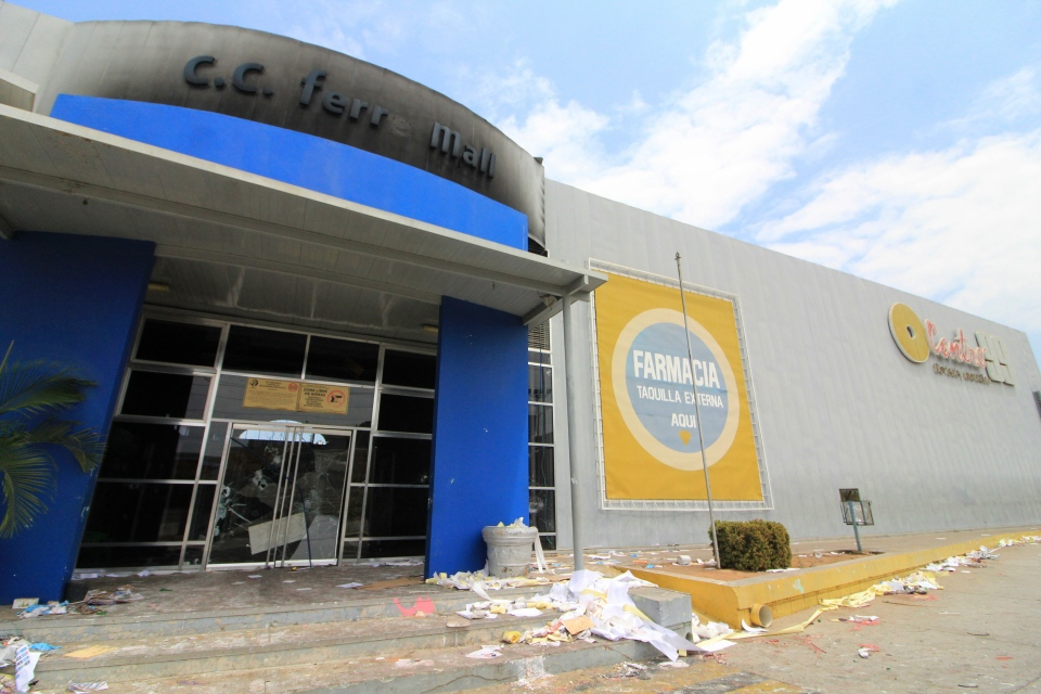 The main entrance of a mall stands burned and damaged after looting the previous day in Maracaibo, Venezuela, Wednesday, March 13, 2019. (AP Photo/Henry Chirinos)