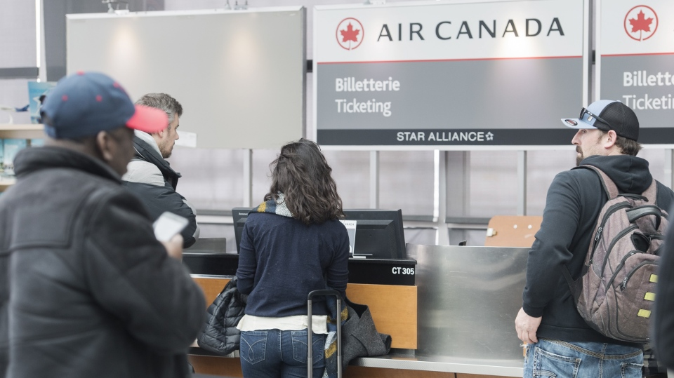 Passengers line up at an Air Canada ticket desk following the cancellation of their flight at Trudeau Airport in Montreal, Wednesday, March 13, 2019, following the government of Canada's decision to ground all Boeing 737 Max 8 aircraft from departing, arriving or flying over Canadian airspace. (THE CANADIAN PRESS/Graham Hughes)