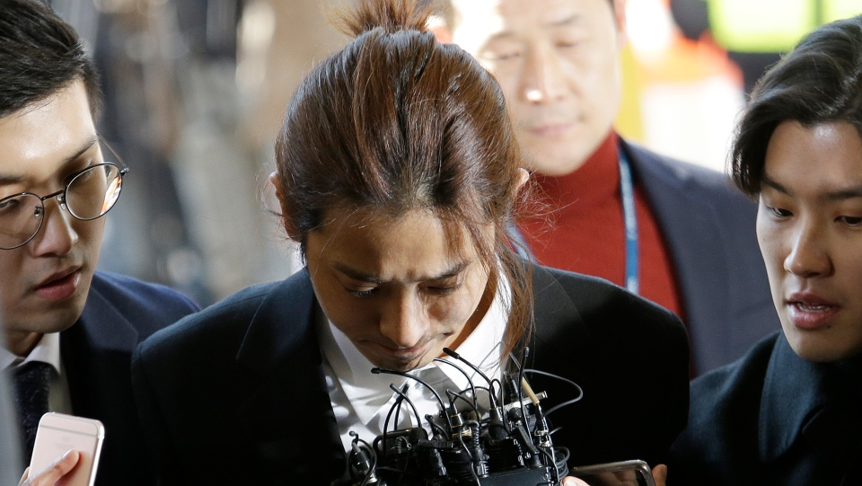 K-pop singer Jung Joon-young, center, arrives at the Seoul Metropolitan Police Agency in Seoul, South Korea, Thursday, March 14, 2019. (AP Photo/Ahn Young-joon)