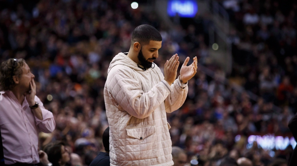Toronto rapper Drake applauds during second half NBA basketball action between the Golden State Warriors and Toronto Raptors in Toronto on Saturday January 13, 2018. THE CANADIAN PRESS/Cole Burston