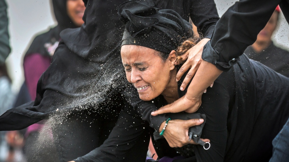 An Ethiopian relative of a crash victim throws dirt in her own face after realizing that there is nothing physical left of her loved one, as she mourns at the scene where the Ethiopian Airlines Boeing 737 Max 8 crashed shortly after takeoff on Sunday killing all 157 on board, near Bishoftu, south-east of Addis Ababa, in Ethiopia Thursday, March 14, 2019. (AP Photo/Mulugeta Ayene)