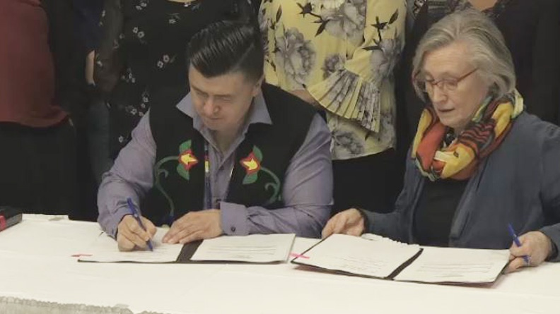 Eskasoni Chief Leroy Denny and Crown-Indigenous Relations Minister Carolyn Bennett sign a 10-year agreement that will grant more than $600 million to Nova Scotia's Mi'kmaq education authority.