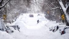 A woman shovels snow