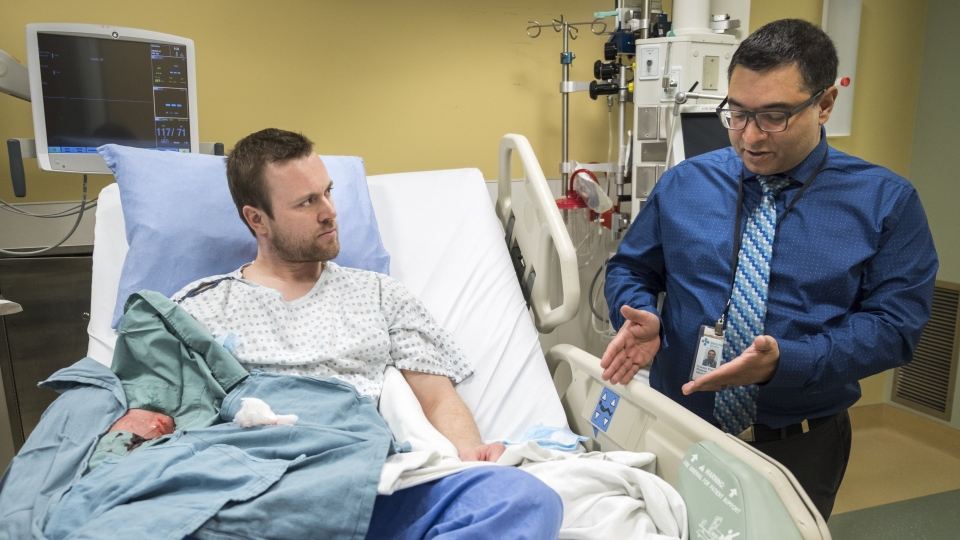 Dr. Aneal Khan, right, a University of Calgary researcher, and patient Josh McQuillin, of Prince George, B.C., who is the first Canadian in history to receive a direct intravenous injection gene replacement therapy, at the University of Calgary's clinical trials unit in Calgary, Alta., Thursday, March 14, 2019. THE CANADIAN PRESS/Jeff McIntosh
