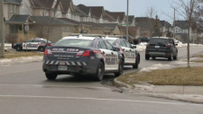 Three police cruisers on a residential street