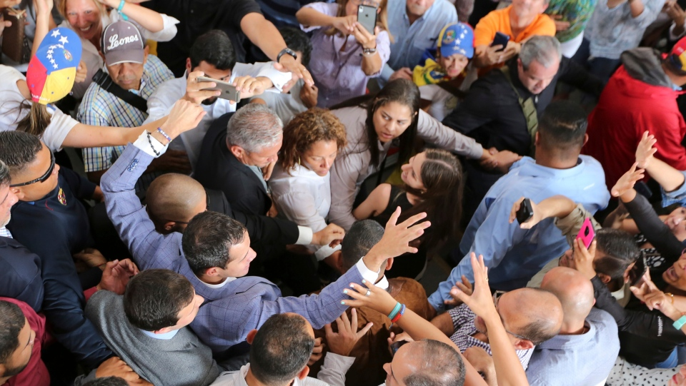 National Assembly President Juan Guaido greets supporters as he arrives to meet with residents in the Hatillo municipality of Caracas, Venezuela, Thursday, March 14, 2019. (AP Photo/Fernando Llano)