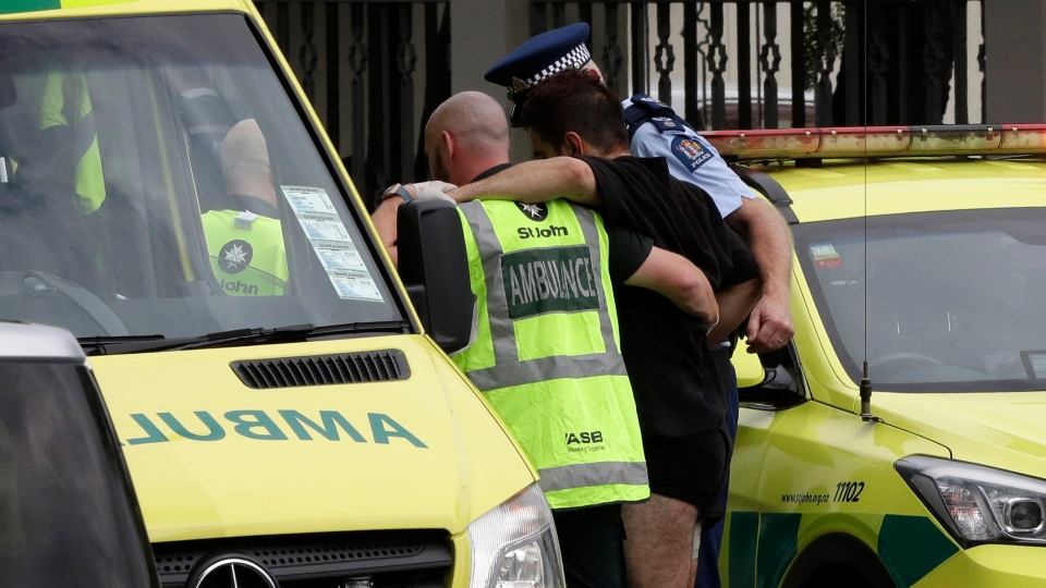 Police and ambulance staff help a wounded man from outside a mosque in central Christchurch, New Zealand, Friday, March 15, 2019. (AP Photo/Mark Baker)