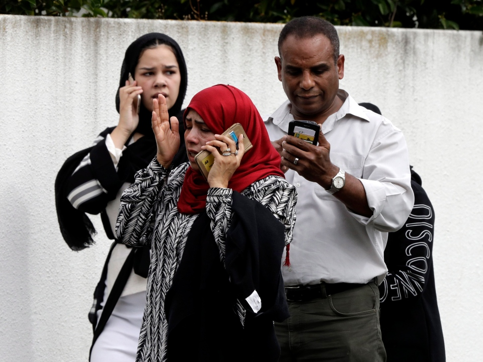 People wait outside a mosque in central Christchurch, New Zealand, Friday, March 15, 2019. Many people were killed in a mass shooting at a mosque in the New Zealand city of Christchurch on Friday, a witness said. (AP Photo/Mark Baker)