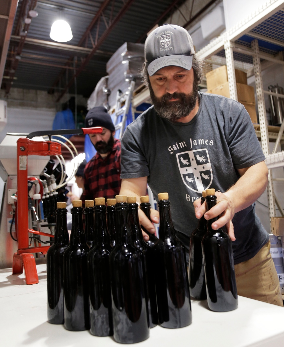 In this March 4, 2019, photo, brewery founder Jamie Adams, right, and John Condzella bottle a batch of their Dubbel beer at the St. James Brewery in Holbrook, N.Y. (AP Photo/Seth Wenig)