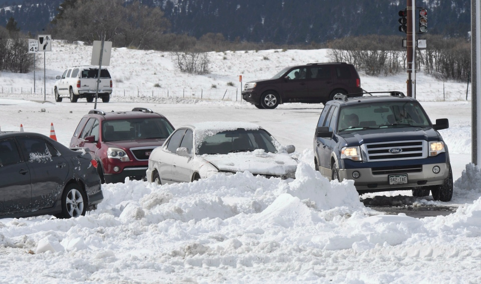 A car drives through an obstacle course of cars that were abandoned in Wednesday's storm in Monument, Colo., on Thursday, March 14, 2019. (Jerilee Bennett/The Gazette via AP)
