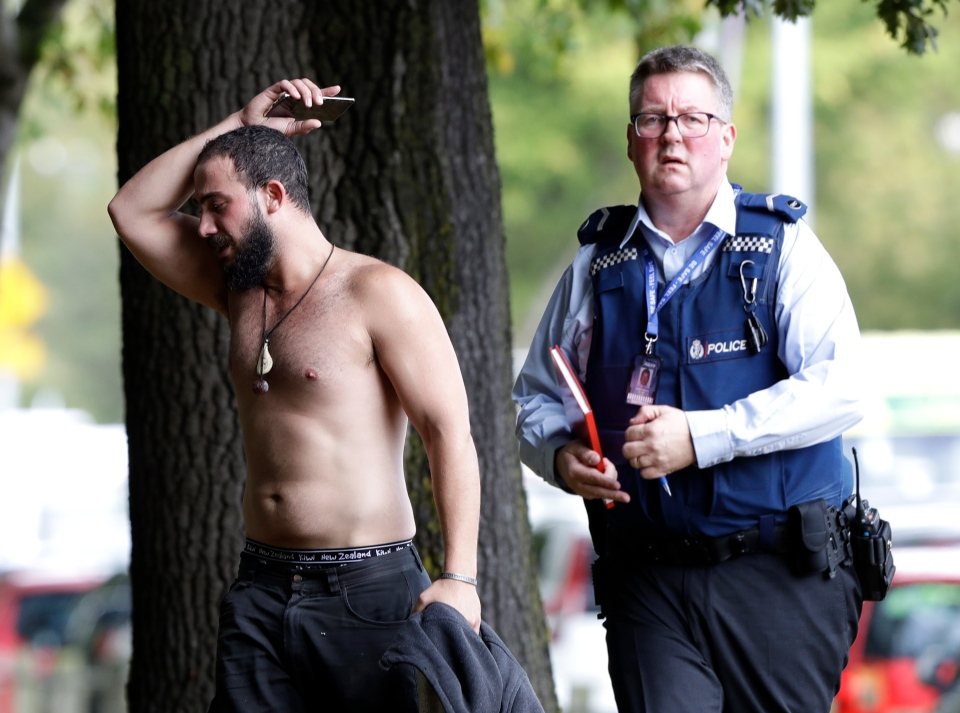 A police officer escorts a man away from a mosque in central Christchurch, New Zealand, Friday, March 15, 2019. (AP Photo/Mark Baker)