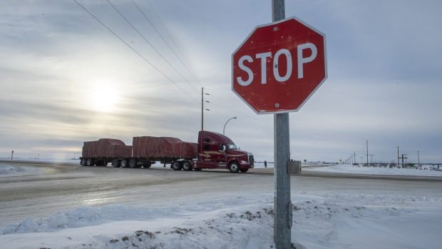 A truck goes through the intersection near the memorial for the 2018 crash where 16 people died and 13 injured when a truck collided with the Humboldt Broncos hockey team bus, at the crash site on Wednesday, January 30, 2019 in Tisdale, Saskatchewan. (THE CANADIAN PRESS/Ryan Remiorz)