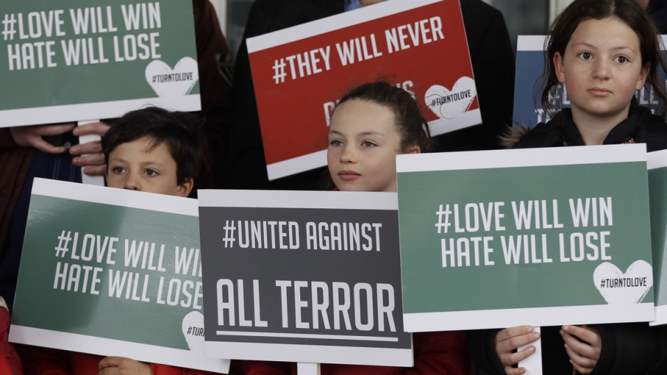 Young demonstrators hold banners from multi-faith group 'Turn to Love' during a vigil at New Zealand House in London, on March 15, 2019. (Kirsty Wigglesworth / AP)