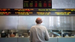 A man watches the financial numbers at the TMX Group in Toronto's financial district on May 9, 2014. (THE CANADIAN PRESS/Darren Calabrese)