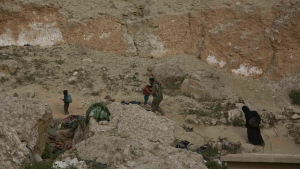 A woman and her children, who left the besieged Islamic State-held village of Baghouz, Syria, scramble over a rocky hillside, assisted by a U.S-backed Syrian Democratic Forces fighter Thursday, March 14, 2019. (AP Photo/Maya Alleruzzo)