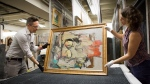 """This August 2017 photo shows """"Woman-Ochre,"""" a painting by Willem de Kooning, being readied for examination by University of Arizona Museum of Art staff Nathan Saxton, left, and Kristen Schmidt in Tucson, Ariz. (Robert Demers/University of Arizona Communications via AP)"""