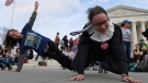 Stephanie Firestone, left, and Alice Wisbiski, right, both fans of Supreme Court Associate Justice Ruth Bader Ginsburg, do exercises on the steps of the Supreme Court in Washington, Friday, March 15, 2019, to celebrate Ginsburg's upcoming birthday 86th birthday. (AP Photo/Susan Walsh)