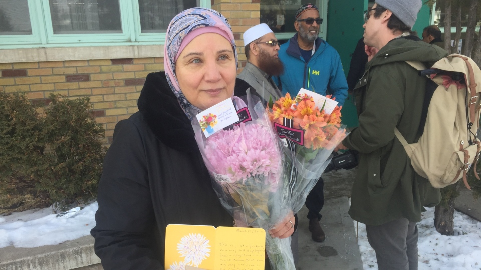 Hanan Elbardouh holds flowers and cards that have been sent to the Islamic Association of Saskatchewan's Main Mosque, following Christchurch's attacks. (Laura Woodward/CTV Saskatoon)