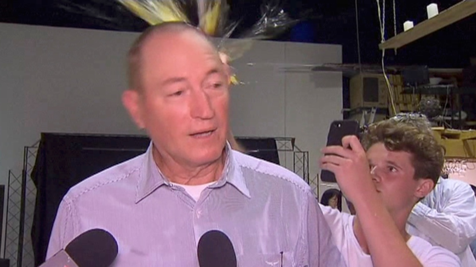In this image made from video, a teenager breaks an egg on the head of Senator Fraser Anning while he holds a press conference, Saturday, March 16, 2019, in Melbourne, Australia. (AP Photo)