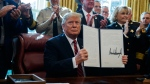 President Donald Trump signs the first veto of his presidency in the Oval Office of the White House, Friday, March 15, 2019, in Washington. Trump issued the first veto, overruling Congress to protect his emergency declaration for border wall funding. (AP / Evan Vucci)
