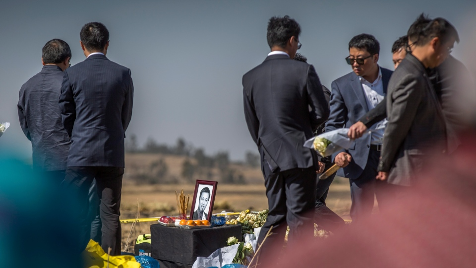A photograph of a Chinese crash victim is placed next to incense and an offering of fruit, as relatives mourn and grieve at the scene where the Ethiopian Airlines Boeing 737 Max 8 crashed shortly after takeoff on Sunday killing all 157 on board, near Bishoftu, south-east of Addis Ababa, in Ethiopia Friday, March 15, 2019. Analysis of the flight recorders has begun in France, the airline said Friday, while in Ethiopia officials started taking DNA samples from victims' family members to assist in identifying remains. (AP Photo/Mulugeta Ayene)