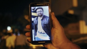A relative shows the picture of Syed Areeb Ahmed, a Pakistani citizen who was killed the Christchurch mosque shooting, on his cell phone outside his home in Karachi, Pakistan, Saturday, March 16, 2019. (AP Photo/Fareed Khan)